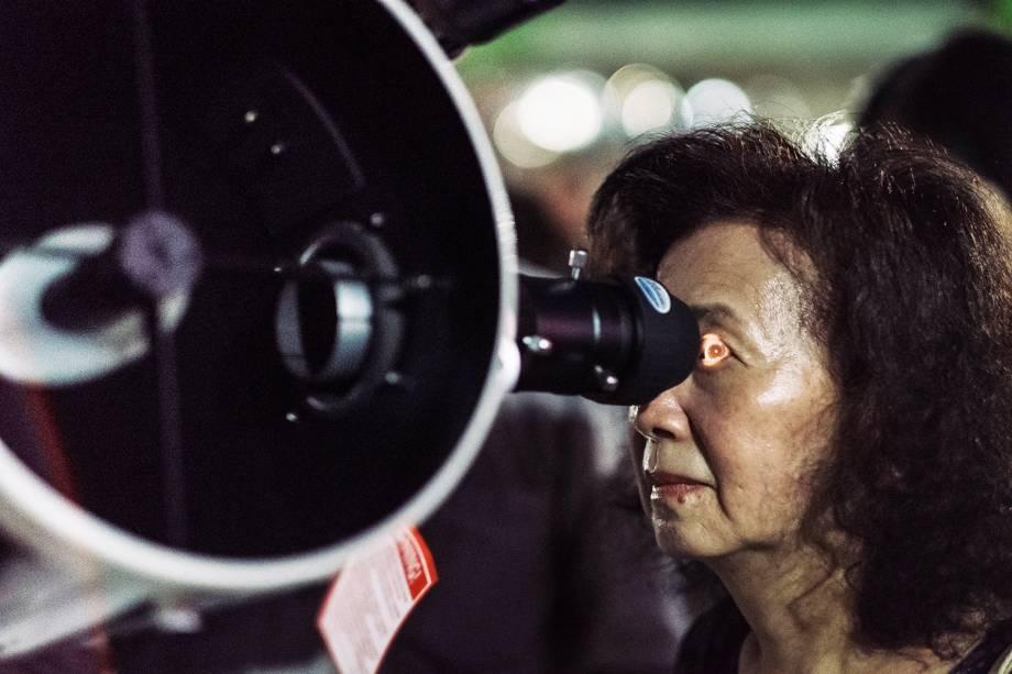 Mulher utiliza telescópio para observar os fenômenos de eclipse lunar e Lua de Sangue, em Taipei, capital de Taiwan - 27/07/2018