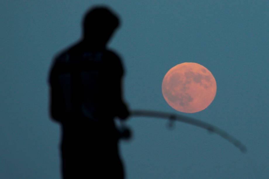 Homem realiza pescaria durante eclipse lunar com 'Lua de Sangue', em Antália, na Turquia - 27/07/2018