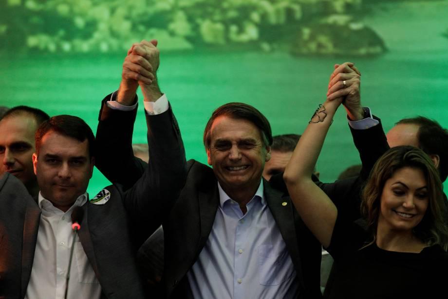 O deputado federal Jair Bolsonaro levanta as mãos com seu filho Flavio Bolsonaro e sua esposa Michelle Bolsonaro durante convenção nacional do PSL, em que foi formalizado como candidato à Presidência da República, no Rio de Janeiro - 22/07/2018
