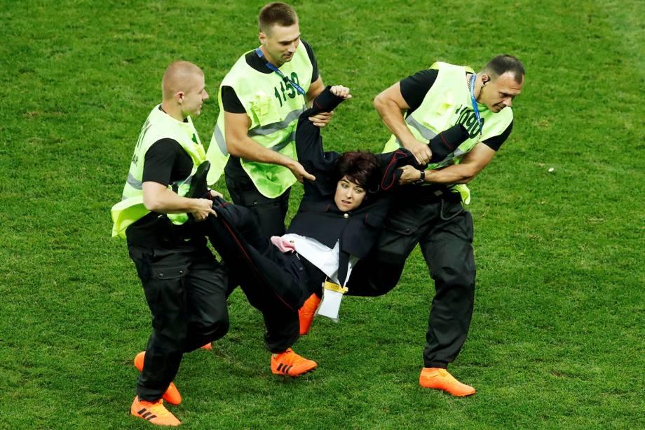 """Uma integrante do grupo de punk rock feminista russo """"Pussy Riot"""" é retirada por seguranças após uma invasão de campo em forma de protesto, durante a partida da final da Copa do Mundo entre França e Croácia - 15/07/2018"""