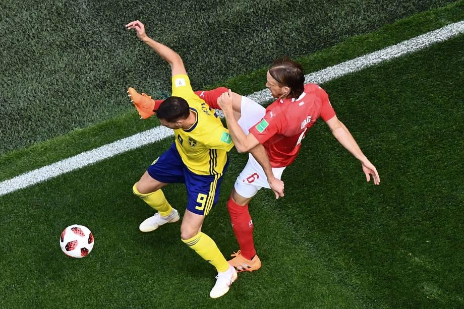 O atacante sueco Marcus Berg disputa a bola com o zagueiro suíço Michael Lang durante as oitavas de final da Copa do Mundo, em São Petesburgo - 03/07/2018