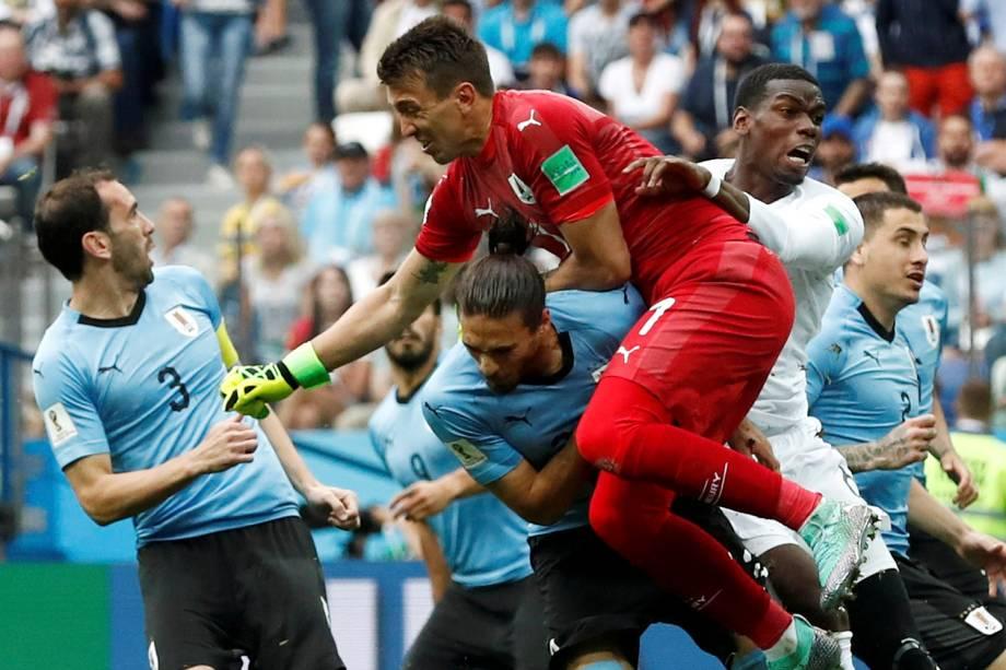 O goleiro uruguaio, Fernando Muslera, sai do gol para tirar uma bola cruzada na área para o francês, Paul Pogba - 06/07/2018
