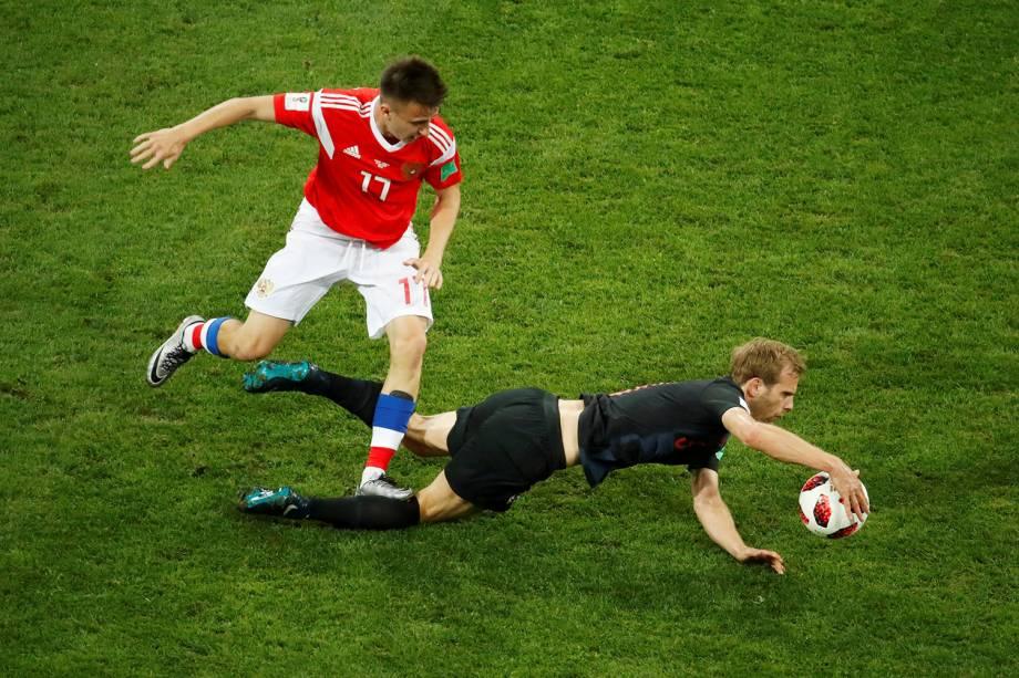 O russo, Aleksandr Golovin, comete uma falta contra o croata, Ivan Strinic, que ao sentir o contato segura a bola com a mão - 07/07/2018