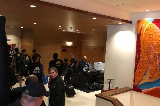 Jogadores aguardam elevador separados por cortina dos outros hóspedes do hotel