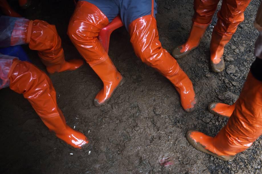 Paramédicos voluntários usam botas no chão lamacento do posto avançado na entrada da caverna de Tham Luang, durante operação de resgate de um time de futebol infantil e seu treinador presos no local - 27/06/2018