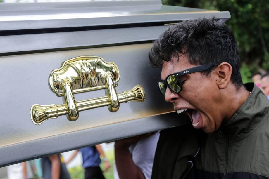 Parente do manifestante Gerald Velazquez, morto a tiros durante confrontos com a polícia em uma igreja perto da Universidade Nacional Autônoma da Nicarágua, carrega o caixão durante seu funeral, em Manágua - 16/07/2018