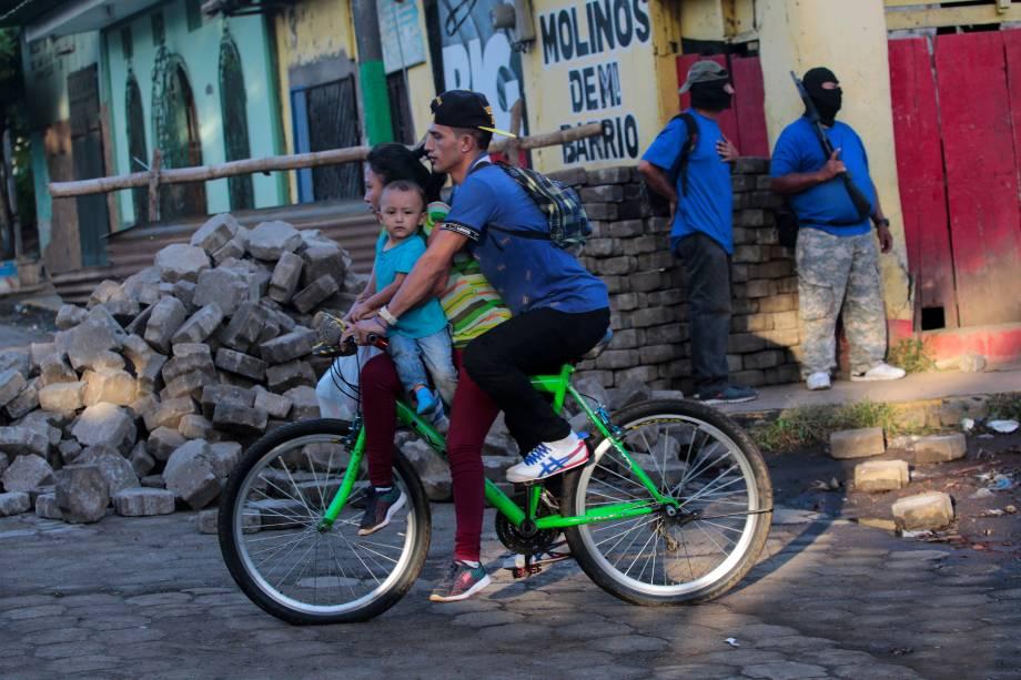 Família passa de bicicleta por manifestantes pró-governo após confrontos na comunidade indígena de Monimbo, em Masaya, Nicarágua - 17/07/2018