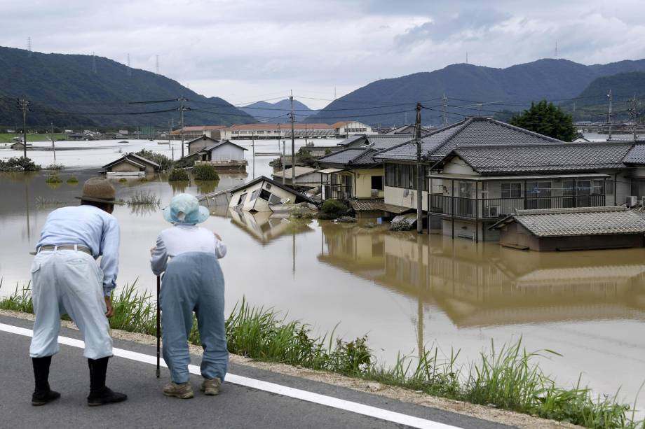 Casal de idosos olha para uma área inundada após a chuva pesada em Kurashiki, Prefeitura de Okayama, no Japão - 08/07/2018