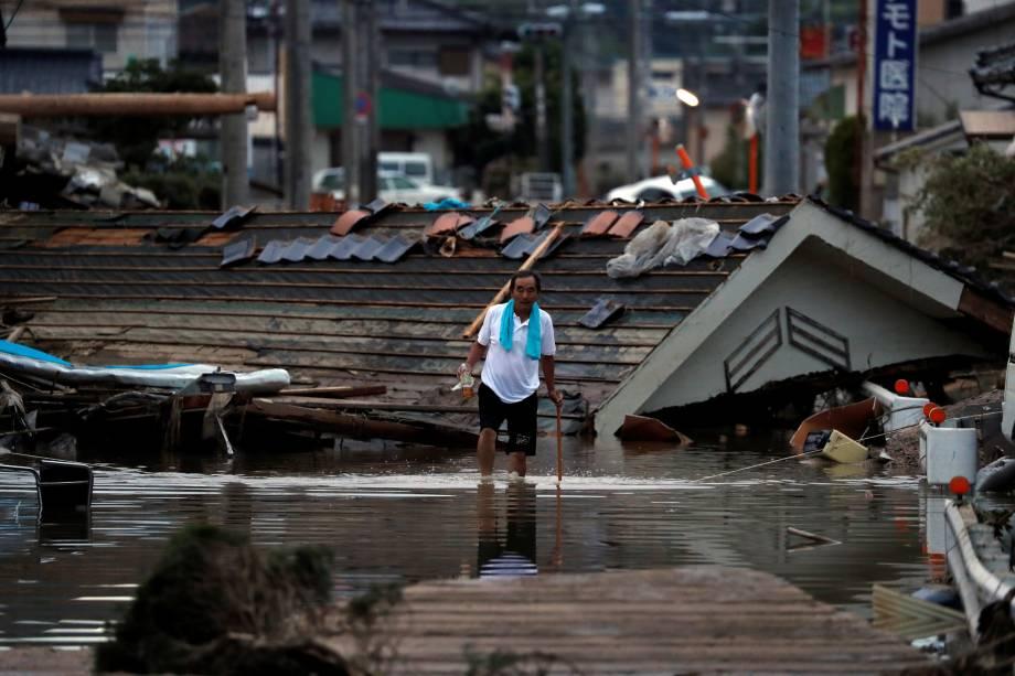 Morador caminha em frente a casas submersas e destruídas em uma área inundada na cidade de Mabi, em Kurashiki, província de Okayama, no Japão - 08/07/2018