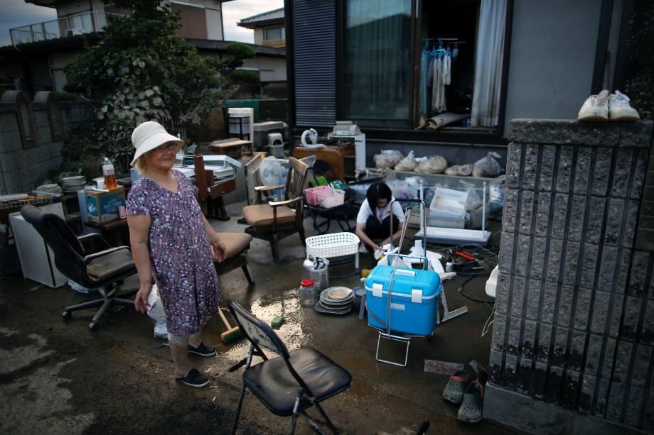 Residentes recolhem seus pertences em uma área inundada em Kurashiki, província de Okayama, Japão - 08/07/2018