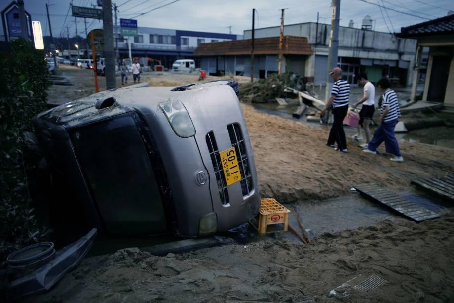 Moradores caminham ao lado de um carro danificado em uma área inundada em Kurashiki, província de Okayama, Japão - 08/07/2018