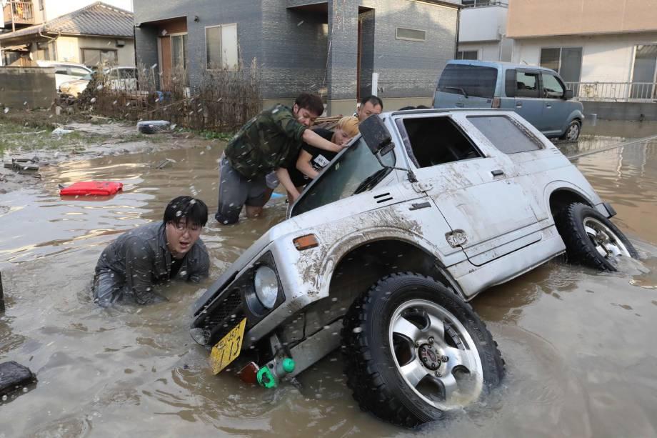 Moradores tentam erguer um veículo preso em uma área atingida pela enchente em Kurashiki, prefeitura de Okayama, no Japão - 09/07/2018