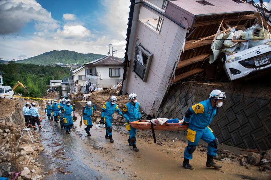 Policiais chegam para trabalhar no resgate de vítimas e retirada de destroços espalhados em uma rua destruída após inundações em Kumano, prefeitura de Hiroshima, no Japão - 09/07/2018