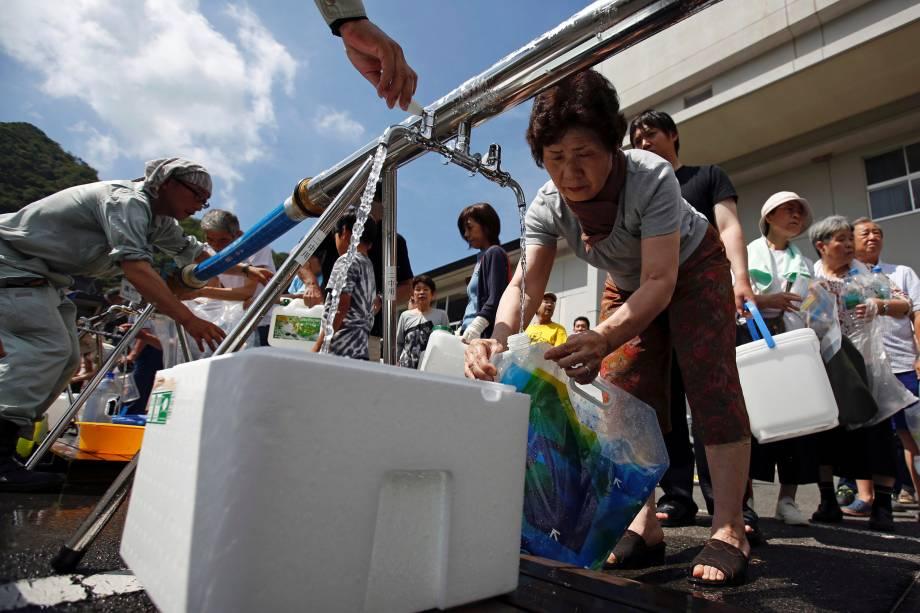 Moradores recebem água perto de uma área inundada na escola secundária Mihara Daini, que tem servido como uma estação de abastecimento de emergência, em Mihara, prefeitura de Hiroshima, no Japão - 09/07/2018