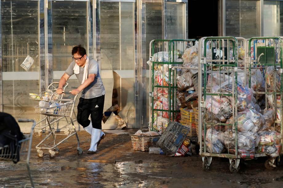 Funcionário de um supermercado empurra um carrinho, com itens enlameados, em uma área inundada na cidade de Mabi em Kurashiki, prefeitura de Okayama, no Japão - 09/07/2018