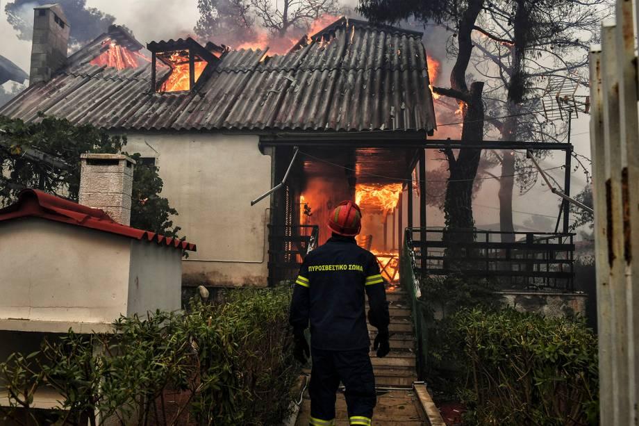 Bombeiro avista uma casa em chamas em Kineta, perto de Atenas, durante um incêndio florestal no qual 300 bombeiros, cinco aeronaves e dois helicópteros foram mobilizados para enfrentar a situação - 23/07/2018