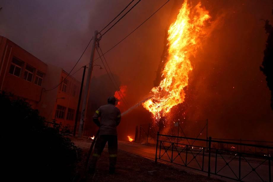 Bombeiro trabalha para conter as chamas de um incêndio florestal em Rafina, perto de Atenas, na Grécia - 23/07/2018