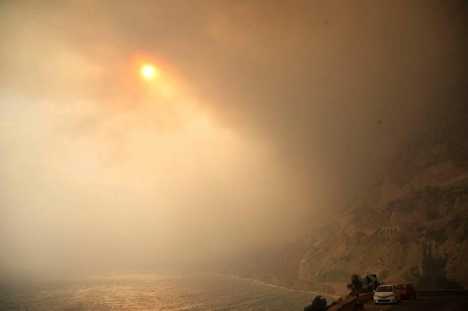 O sol é visto através da densa fumaça de um incêndio florestal na cidade de Kineta, na Grécia - 23/07/2018