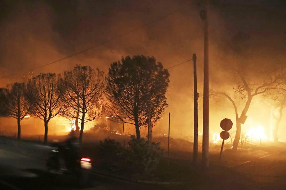 Edifícios queimam atrás de árvores na cidade de Mati, na Grécia. As autoridades regionais declararam estado de emergência nas partes leste e oeste da área metropolitana de Atenas, quando os incêndios se espalharam por florestas de pinheiros e assentamentos à beira-mar em ambos os lados da capital grega - 23/07/2018