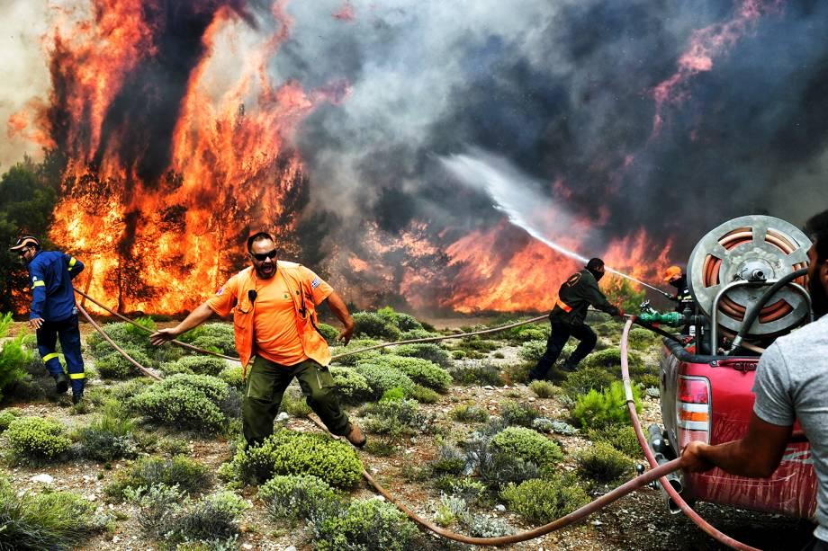 Bombeiros e voluntários trabalham no combate às chamas, durante incêndio florestal no vilarejo de Kineta, próximo de Atenas, Grécia - 24/07/2018