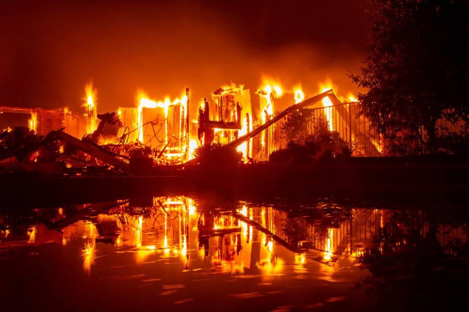 Casa em chamas reflete nas águas de uma piscina durante o incêndio Carr, que atinge a cidade de Redding, na Califórnia - 27/07/2018