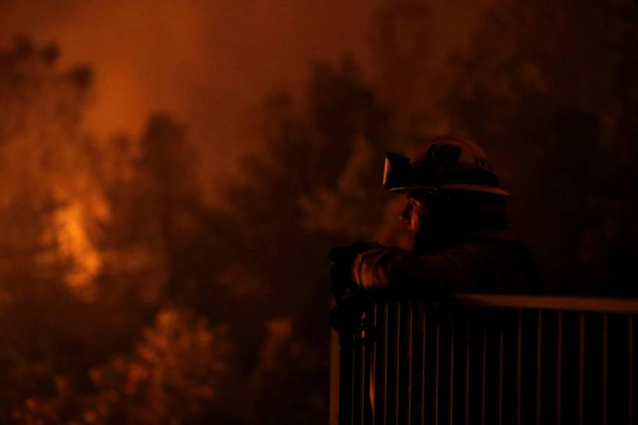 O bombeiro Zach Hallums é visto enquanto seus companheiros lutam contra o incêndio Carr abaixo de um cânion ao oeste de Redding - 27/07/2018