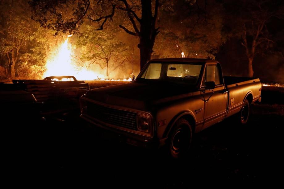 Chamas do incêndio florestal Carr queimam atrás de uma caminhonete na cidade de Redding, na Califórnia - 27/07/2018