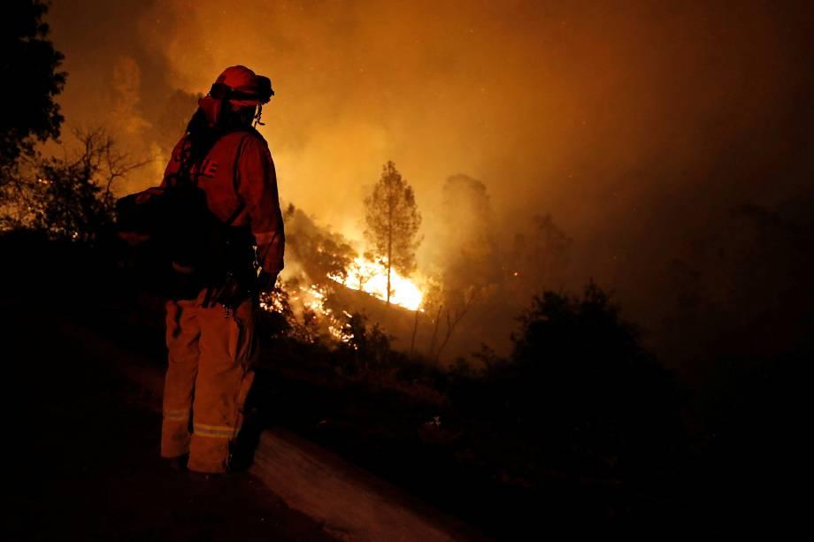 Bombeiro observa as chamas enquanto o fogo avança em direção a casas no oeste da cidade de Redding, na Califórnia - 27/07/2018