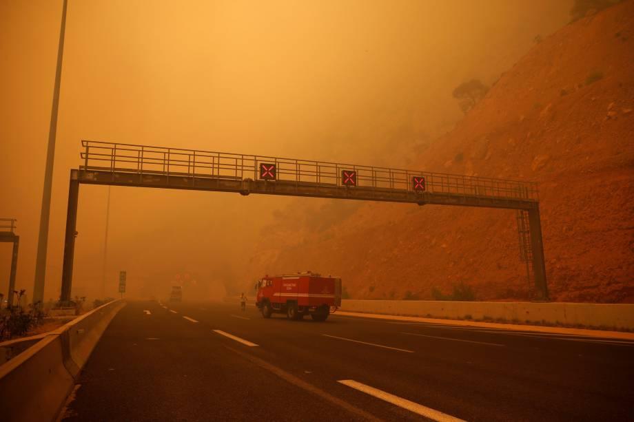 Uma densa camada de fumaça cobre uma estrada durante um incêndio florestal em Kineta, perto de Atenas, na Grécia - 23/07/2018
