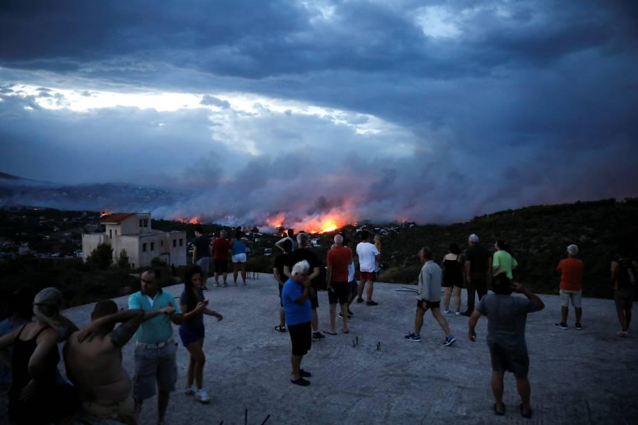 Moradores observam incêndio florestal na cidade de Rafina, perto de Atenas, na Grécia - 23/07/2018