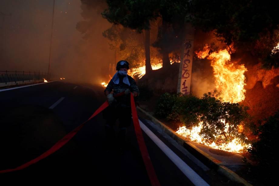 Soldado segura uma mangueira enquanto um incêndio florestal avança sobre a cidade de Rafina, perto de Atenas, na Grécia - 23/07/2018
