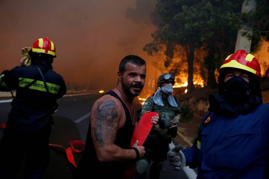 Bombeiros, soldados e moradores carregam uma mangueira enquanto um incêndio florestal atinge a cidade de Rafina, perto de Atenas, na Grécia - 23/07/2018