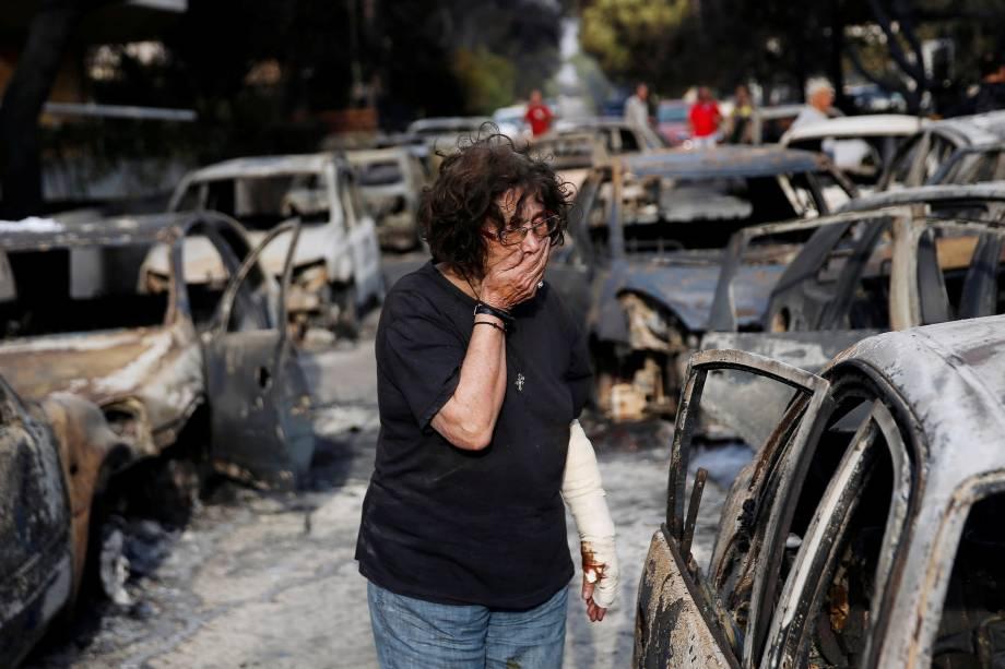 Mulher chora enquanto tenta encontrar seu cachorro, depois de um incêndio na aldeia de Mati, perto de Atenas, na Grécia - 24/07/2018