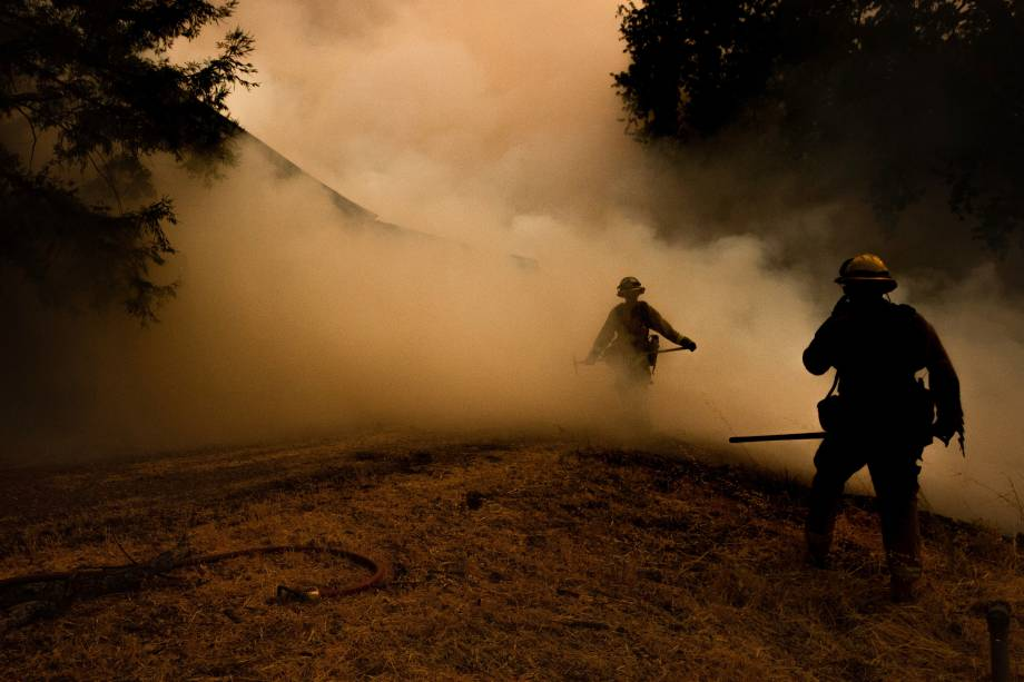 Bombeiros atravessam a fumaça enquanto as chamas se aproximam de uma casa durante o incêndio no complexo de Mendocino, em Lakeport, na Califórnia - 30/07/2018