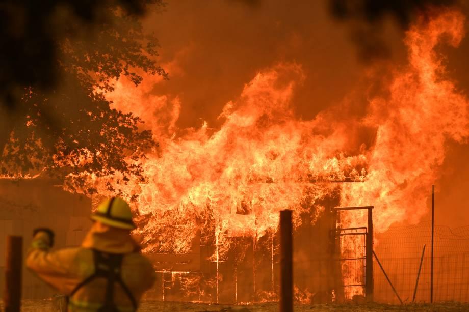 Bombeiro observa enquanto um prédio é consumido pelas chamas do incêndio no Complexo de Mendocino, em Lakeport, na Califórnia - 30/07/2018