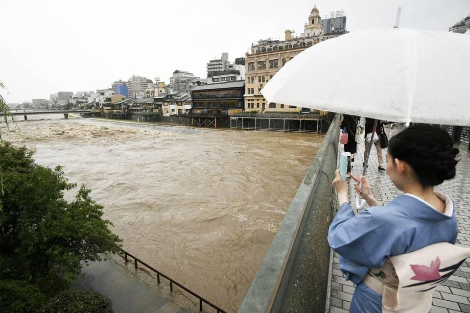 Mulher tira foto de inundação próximo do Rio Kamo, em Kyoto - 05/07/2018