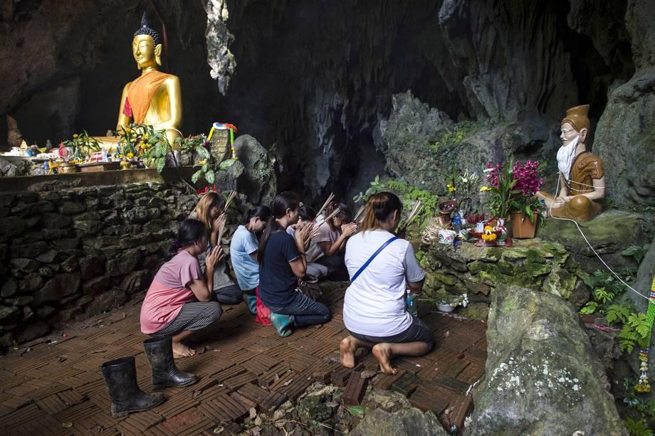 Familiares rezam em um santuário do lado de fora do complexo de cavernas de Tham Luang, antes do resgate dos jovens presos na caverna inundada em Chiang Rai, na Tailândia - 05/07/2018