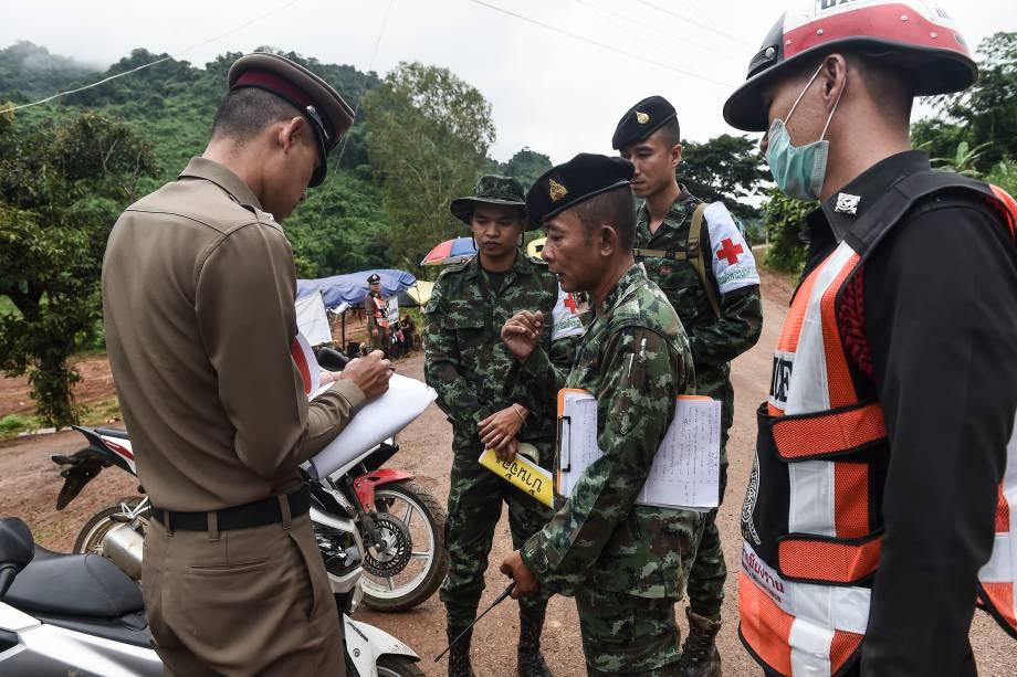 Policial tailandês fala com um soldado na área externa do complexo de cavernas Tham Luang durante as operações de resgate dos 12 meninos e seu treinador presos no local - 08/07/2018