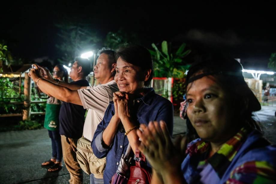 Pessoas aplaudem o momento em que as ambulâncias transportam os meninos resgatados da caverna, na província de Chiang Rai, norte da Tailândia - 08/07/2018