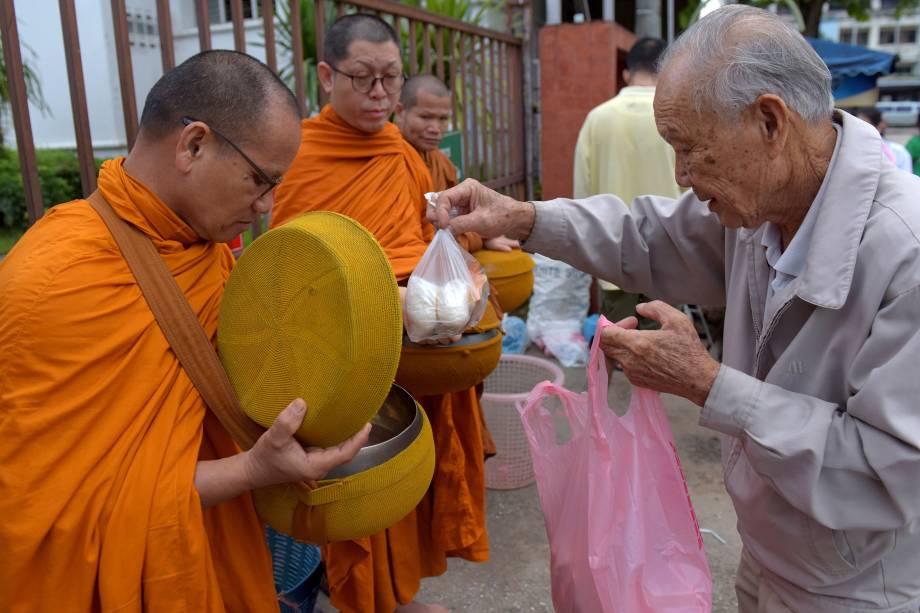 Homem oferece comida a monges budistas perto do hospital onde os meninos resgatados depois de ficarem presos em uma caverna próxima por quase duas semanas foram levados para observação, na cidade de Chiang Rai, no norte da Tailândia - 09/07/2018