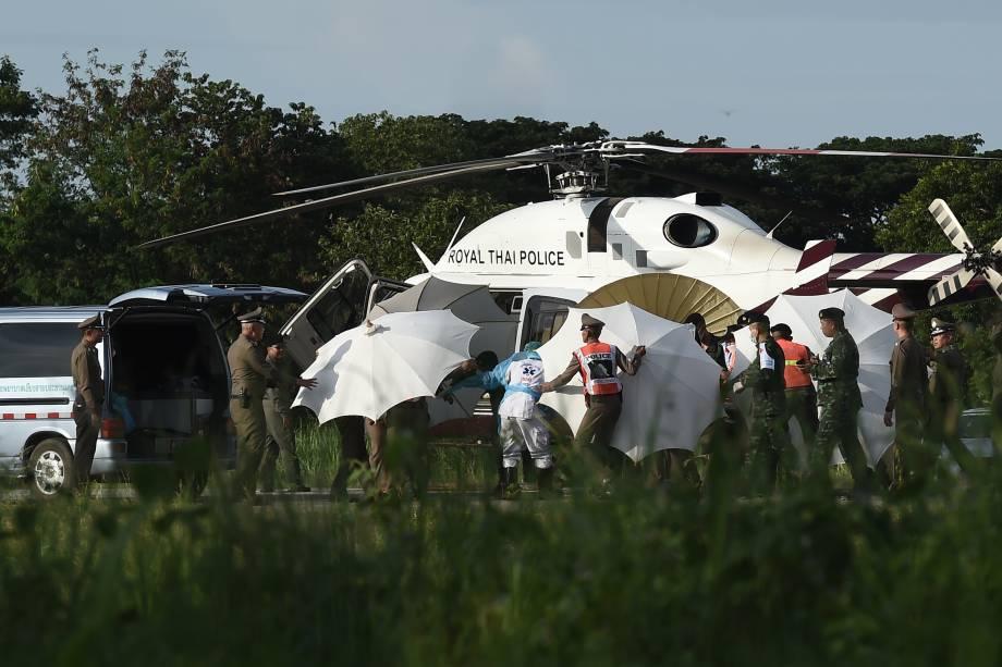 Policiais e militares usam guarda-chuvas para cobrir uma maca perto de um helicóptero e uma ambulância no aeroporto militar em Chiang Rai, durante operação de resgate dos meninos presos em um caverna no norte da Tailândia - 09/07/2018