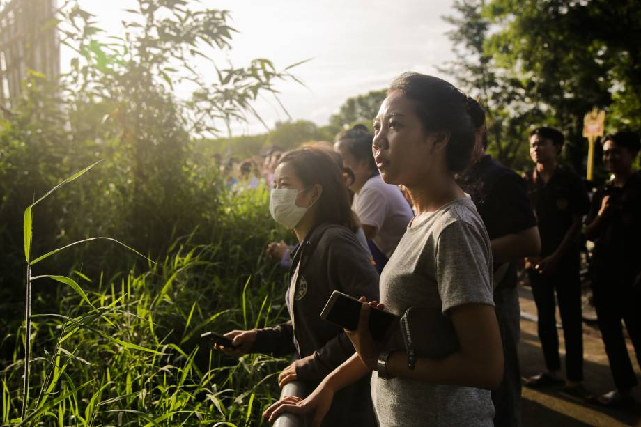 Pessoas assistem e aplaudem enquanto as ambulâncias transportam alguns dos estudantes resgatados do complexo de cavernas Tham Luang para um hospital em Chiang Rai, norte da Tailândia - 09/07/2018