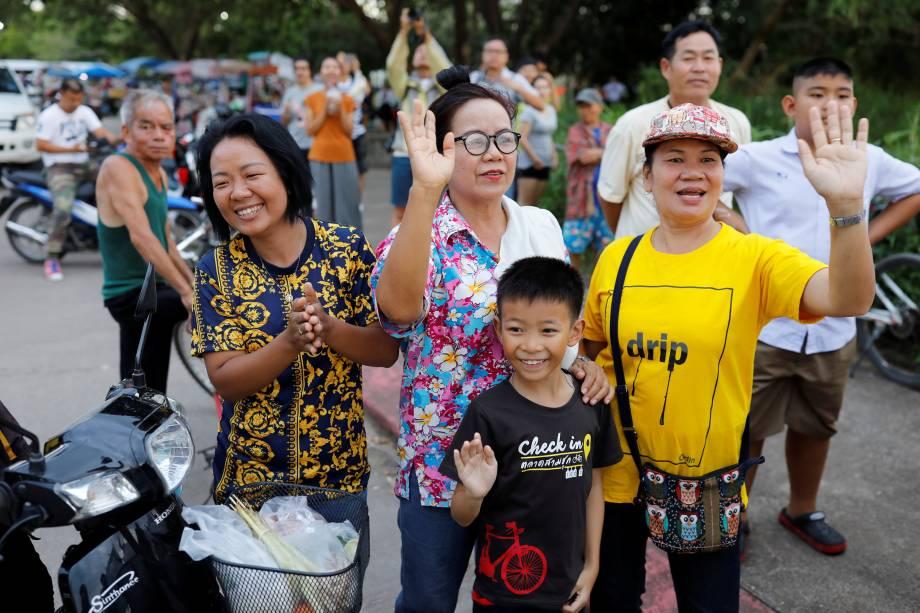 Espectadores acenam enquanto uma ambulância carregando estudantes resgatados da caverna deixa um aeroporto militar em Chiang Rai, norte da Tailândia - 10/07/2018