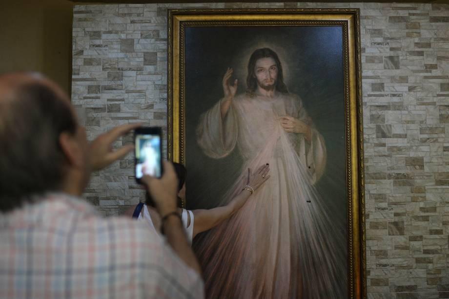 Fiéis católicos rezam diante de uma imagem de Jesus Cristo, atingida por balas durante um ataque das forças do governo Daniel Ortega à igreja da Divina Misericórdia em Manágua, na Nicarágua - 20/07/2018