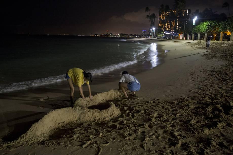 Turistas fazem barreiras com areia, antes da passagem do furacão Lane na praia de Waikiki, em Honolulu, Havaí - 23/08/2018