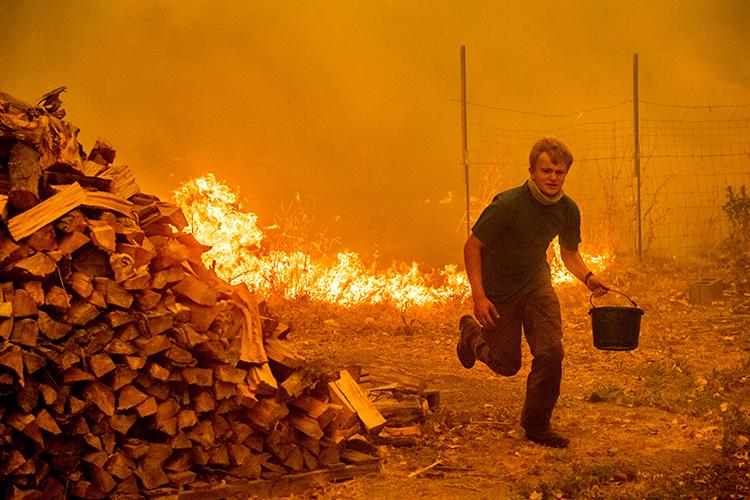 Alex Schenck tenta salvar sua casa de incêndio florestal no Complexo Mendocino, Califórnia - 04/08/2018