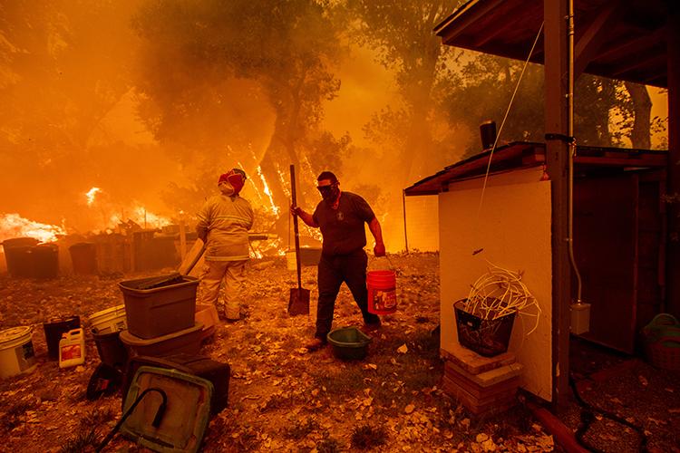 Lane Lawder, morador de área próxima a cidade de Clearlake Oaks tenta salvar sua casa de incêndio na Califórnia - 04/08/2018