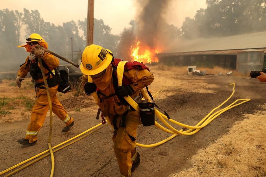 Bombeiros carregam mangueiras enquanto um celeiro arde nas chamas do incêndio River Fire em Lakeport, na Califórnia - 01/08/2018