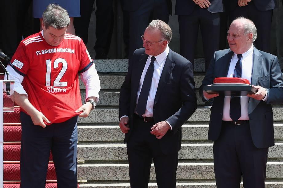 O governador da Baviera, Markus Söder (esq), é visto com camiseta do Bayern de Munique, juntamente com o CEO do clube, Karl-Heinz Rummenigge, e o presidente do Conselho de Administração Uli Hoeness - 09/05/2018