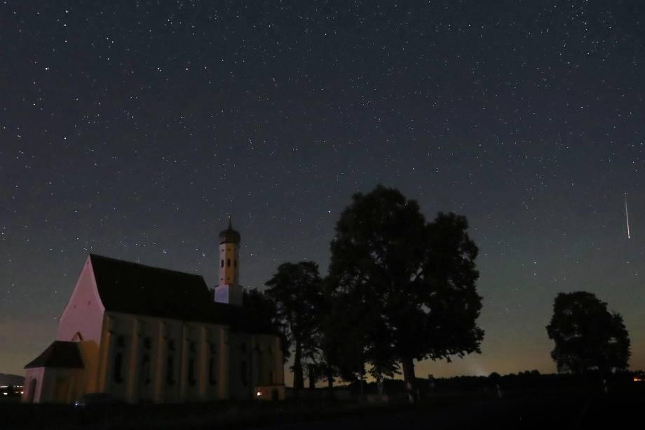 Meteoro atravessa o céu noturno atrás da igreja de peregrinação de Sankt Coloman, em Fuessen, sudoeste da Alemanha, durante a chuva anual de meteoros Perseidas - 12/08/2018